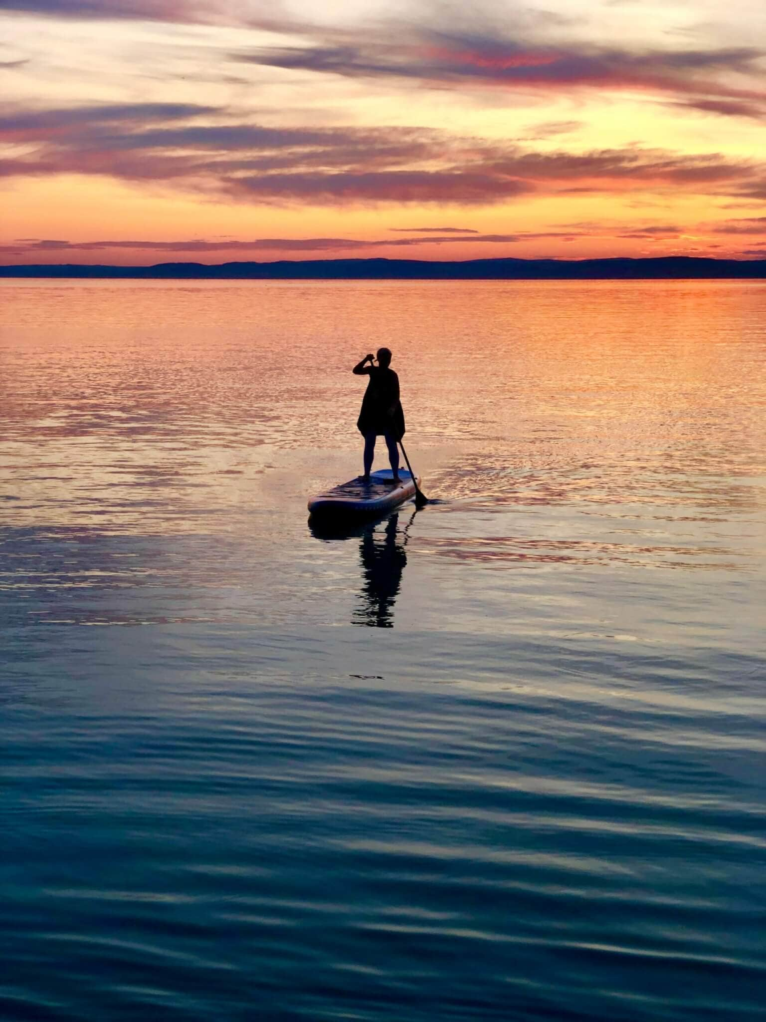 silhouette of person standing on paddle boat during golden hour